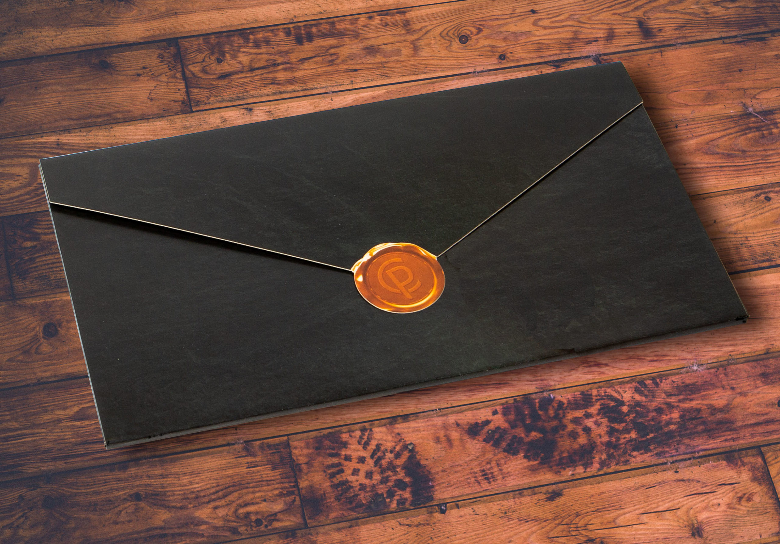 Closed business to business mailer with classy style and orange diecut seal on wooden table